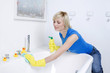 Woman with rubber gloves, cleaning the bathtub