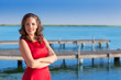 Brunette woman dress in red smiling relaxed on a lake