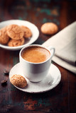 Cup of espresso and biscotti on dark wooden table