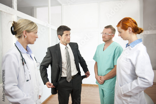 Businessman showing empty pockets to doctors