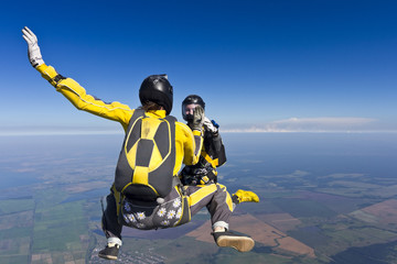 Two girls holding hands parachutist.