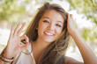 Attractive Mixed Race Girl Portrait with Okay Hand Sign Outdoors