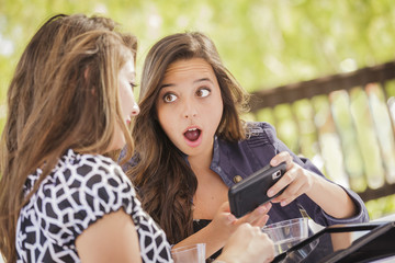 Shocked Mixed Race Girls Working on Electronic Devices