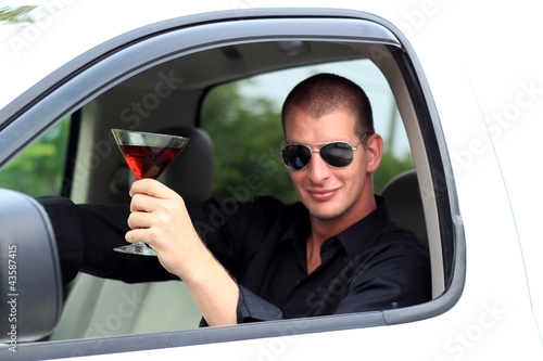 Man In Truck Holding Alcohol Smiling