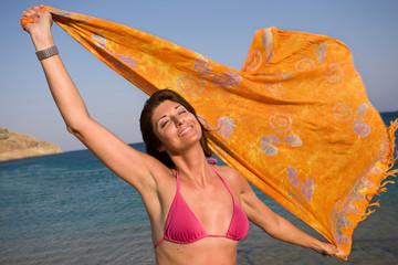 Donna con pareo al mare al vento