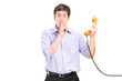 Man holding a telephone and gesturing silence