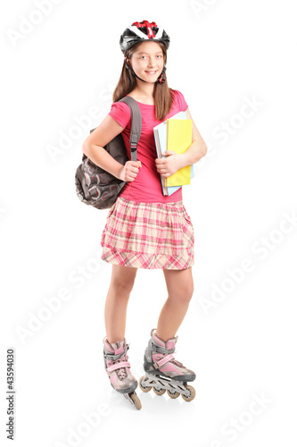 Full length portrait a girl on rollers holding notebooks