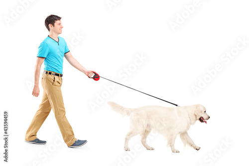Full length portrait of a young man walking a dog