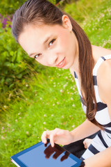 Junge Frau auf der Liegewiese mit Tablet-PC