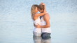 Loving couple embracing and looking at  each other in the sea