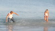 Cheerful couple doing splashes to each other in the summer sea