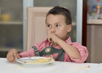 Junge beim Nudel essen