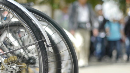 Wheels of parked bicycles with people walking past.