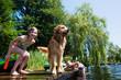 Leinwanddruck Bild - children playing with their Golden Retriever dog on a lake
