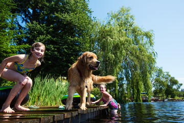 Happy Children playing with their dog on a lake
