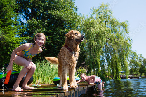 Leinwanddruck Bild children playing with their Golden Retriever dog on a lake