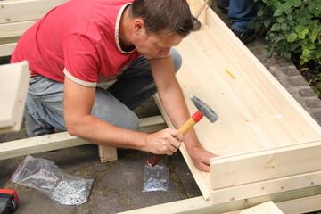 Mann beim Aufbau eines Gartenhauses