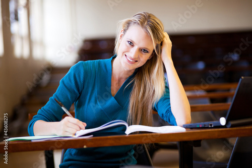 happy female college student sitting in classroom