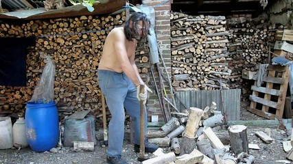 shirtless man chopping wood