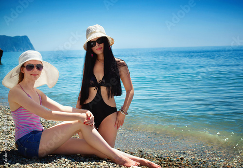 Young happy beautiful woman lying on sea beach