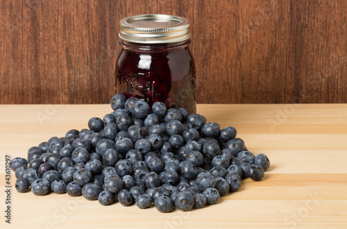 Fresh blueberries on wooden table with jam