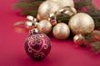Weihnachtliche Dekoration mit goldenen Kugeln und Tanne auf rote