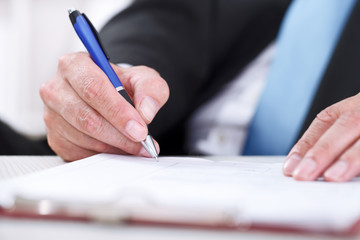 Close up of businessman signing a contract.