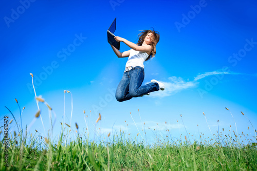 Jumping woman with laptop