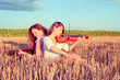 Two young women playing guitar and violin outdoors. Split toning