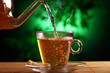 Hot green tea in glass teapot and cup