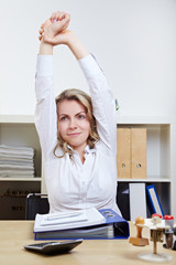 Frau dehnt sich im Büro