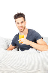 Smiling man is drinking orange juice in the bed