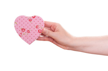 Weibliche Hand hält ein rosa Herz nach vorne