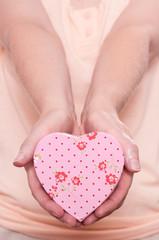 Frau hält ein rosa Herz mit beide Händen nach vorne