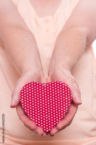 Zwei Hände halten ein rotes Herz nach vorne