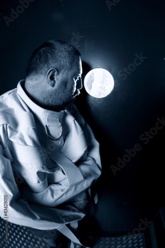 Mentally ill man looking out his cell