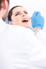 Dentist in blue medical gloves examines the oral cavity