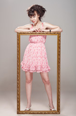 Beautiful girl posing in a pink dress, stilettos and frame