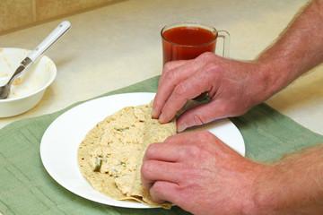 Hands Rolling Salmon Spread in Tortilla