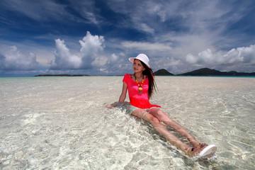 南国沖縄のビーチでリラックスする女性