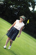 An old lady in golf attire standing in a golf course