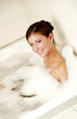 A lady having a bubble bath in the bathtub