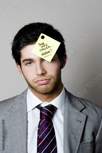 Businessman with a phone message sticking on his forehead
