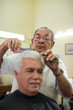 Old barber cutting hair to client in barber shop