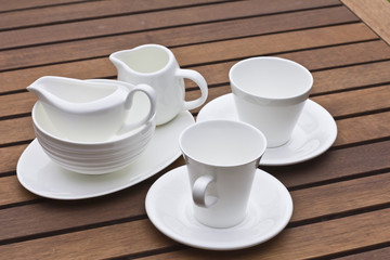 A lot of white crockery on wooden background
