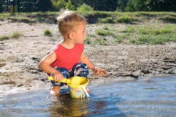 Kleiner Junge am Strand mit Eimer und Schippe