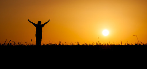 Person celebrating life at sunset