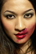 Woman with red lipstick smudged around her lips