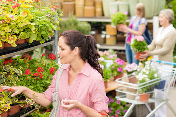 Woman choose potted flower in garden store