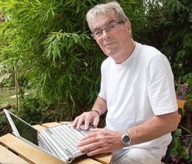 retraité actif et moderne, utilisant un ordinateur portable
